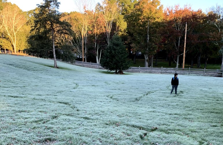 Boy making paths through a frosty New England field