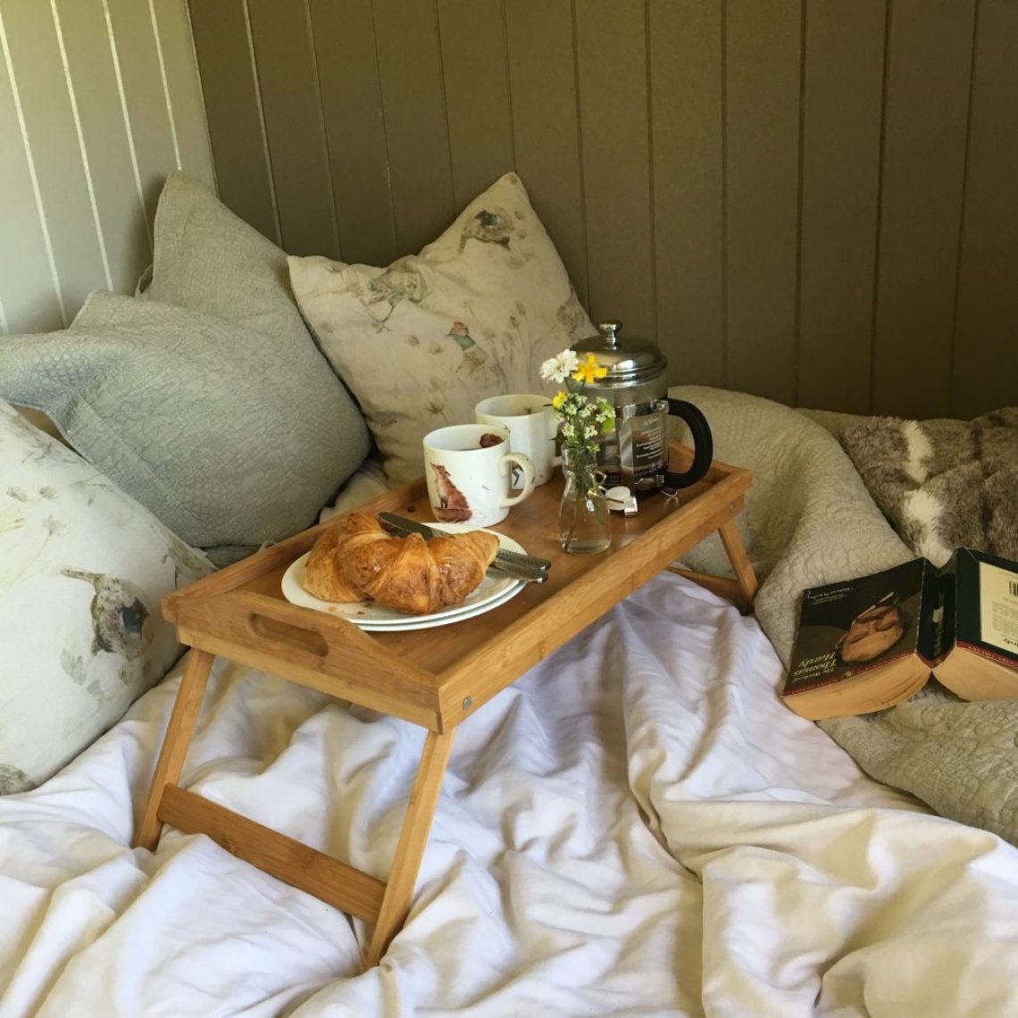 A wooden tray is set with breakfast and a Thomas Hardy novel on the bed in the Pleasant Pheasant at Farmstead Glamping