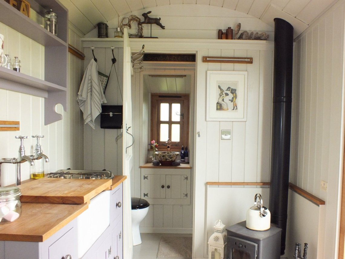 inside the Happy Hare shepherd hut showing the en suite shower room, wood burner and Kitchen