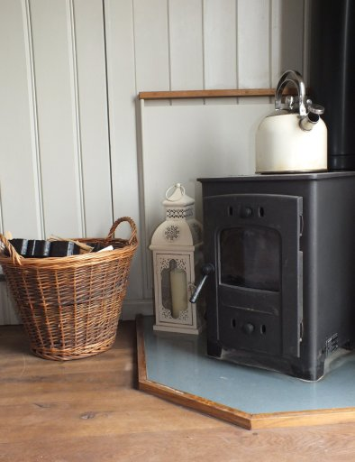 A small woodburning stove with a kettle on top