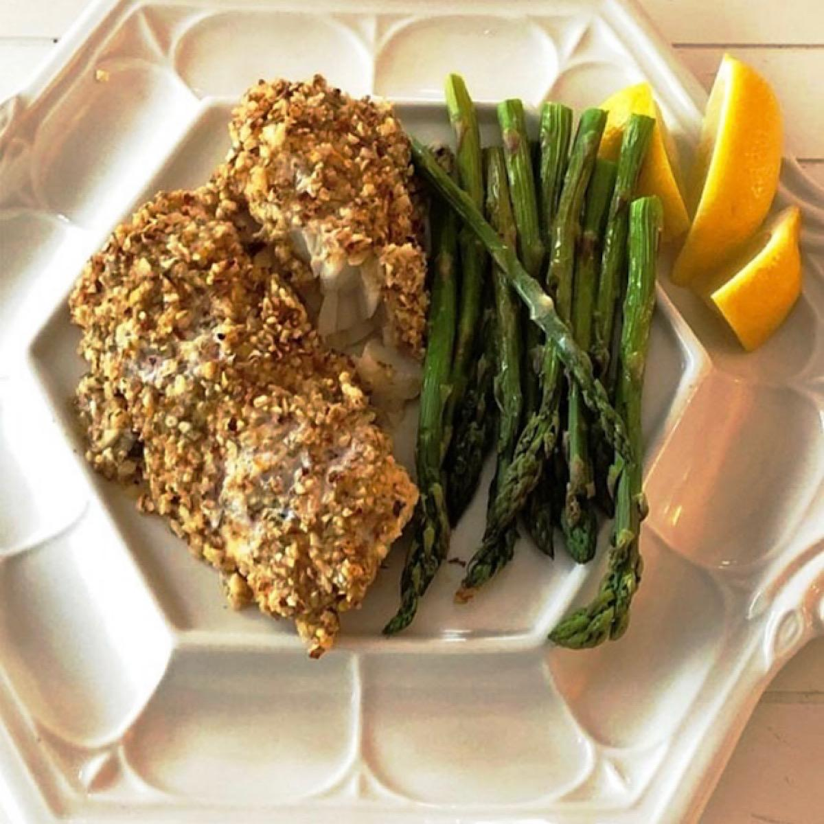Low carb dinner of almond-crusted cod with asparagus spears