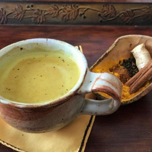 Cup of golden milk latte with turmeric and chai spices