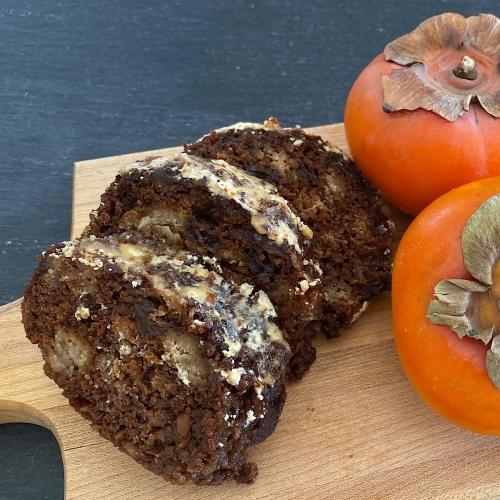3 slices of persimmon steamed pudding on a board with persimmons
