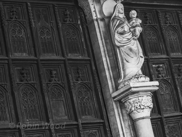 A statue of Mary holding Jesus flanked by old wooden doors.