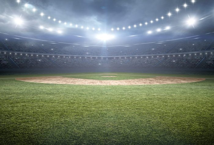 View of baseball infield from center field grass under bright stadium lights