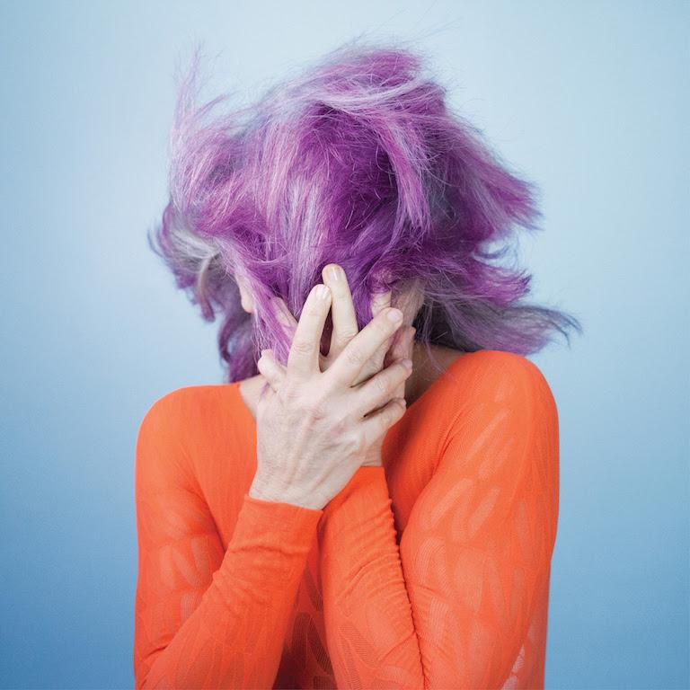 """Atrás do cabelo entre o grisalho e o lilás, Tetê esconde e mostra o rosto moldado em """"Outro Lugar"""""""