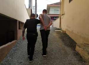Policial conduzindo funcionário de agência envolvido com o assalto - foto da Polícia CIvil