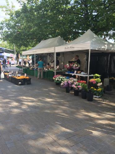 A floral market down a main road in Manchester. These are often found selling foods, flowers, and handmade crafts