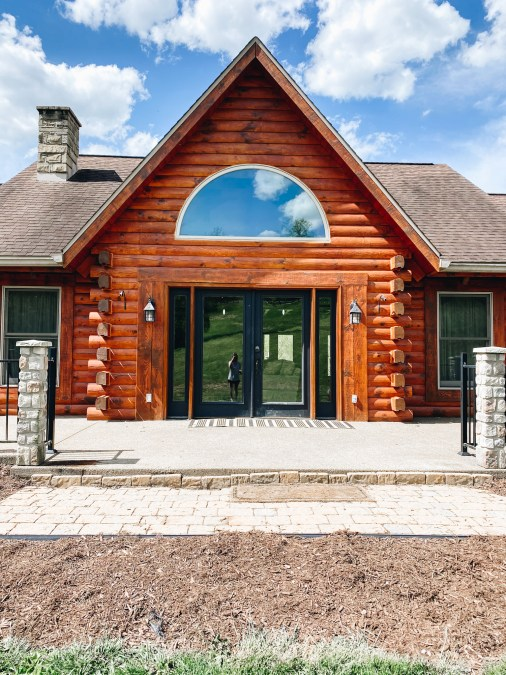 before a front porch refresh | Summer Front Porch by popular Pittsburg life and style blog, Fashionably Late Mom: before image of a log home with double black Fram window doors and a black and white rug.