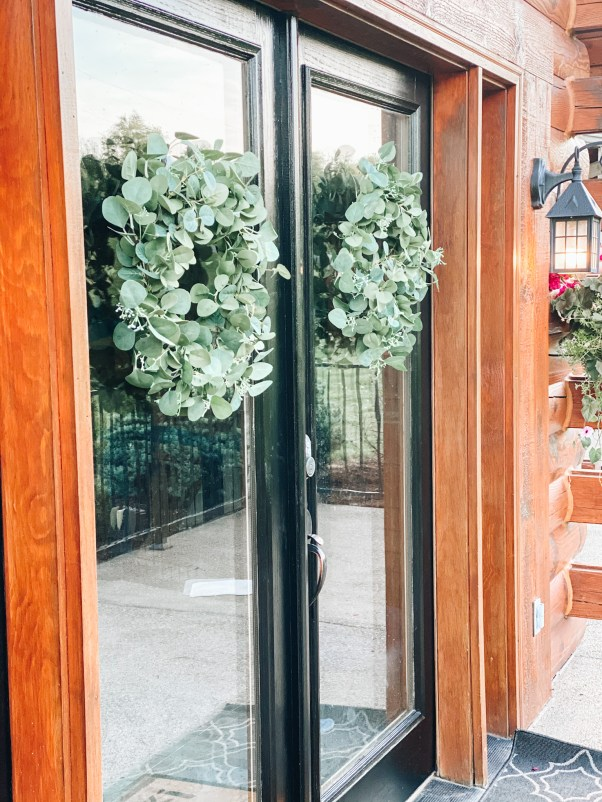 eucalyptus wreaths |  Summer Front Porch by popular Pittsburg life and style blog, Fashionably Late Mom: after image of a front porch on a log home with black frame doors, black planters with pink flowers, hanging potted pink flower planters, and greenery wreaths.