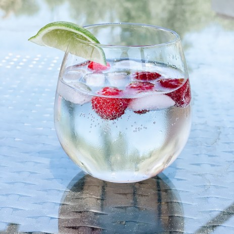 raspberry summer spritzer | Raspberry Spritzer by popular Pittsburg lifestyle blog, Fashionably Late: image of a raspberry spritzer in stemless glass with a lime wedge garnish.