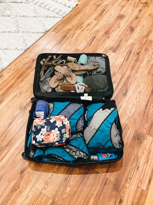 5 Top Packing Tips for your Family Vacation, featured by top Pittsburgh lifestyle blogger, Fashionably Late Mom. | Packing Tips by popular Pittsburgh travel blog, Fashionably Late Mom: image of a packed suitcase laying open on a wooden floor.