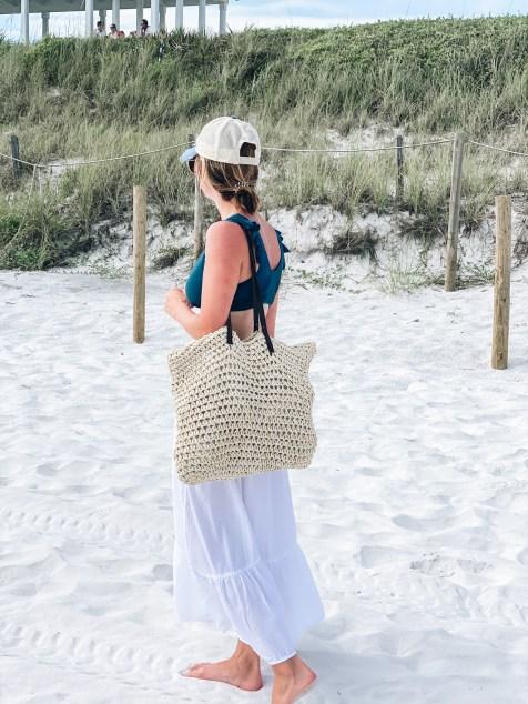 beach bag, straw bag, pool bag, cute beach bags | Cute Beach Bags by popular Pittsburgh fashion blog, Fashionably Late Mom: image of a woman standing on a white sand beach and carrying a straw beach bag.