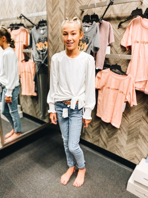Nordstrom Anniversary Sale 2021: Try On Edition featured by top Pittsburgh fashion blogger, Fashionably Late Mom   Nordstrom Anniversary Sale by popular Pittsburgh fashion blog, Fashionably Late Mom: image of a teenage girl wearing a Nordstrom white tie front long sleeve shirt with light wash jeans.