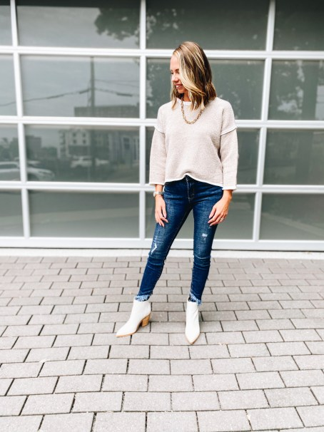 Pink Lily by popular Pittsburgh fashion blog, Fashionably Late Mom: image of a woman wearing a Pink Lilly  cream sweater, gold chain necklace, distressed jeans, and white ankle boots.