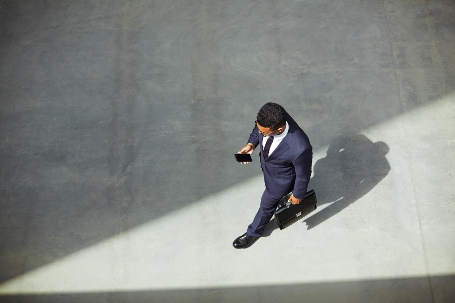 Elegant businessman with briefcase using cellphone on the move