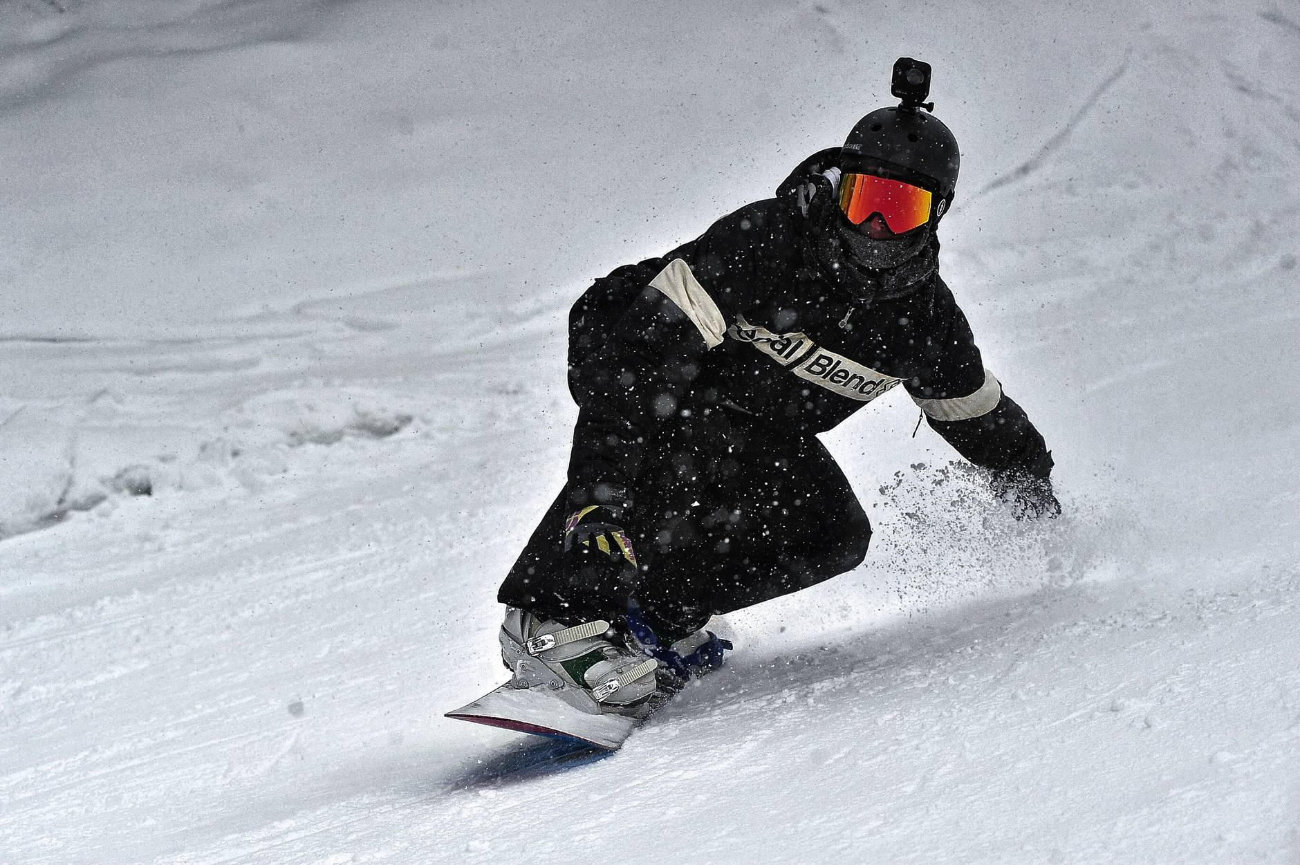 person in black jacket and black pants riding on snowboard
