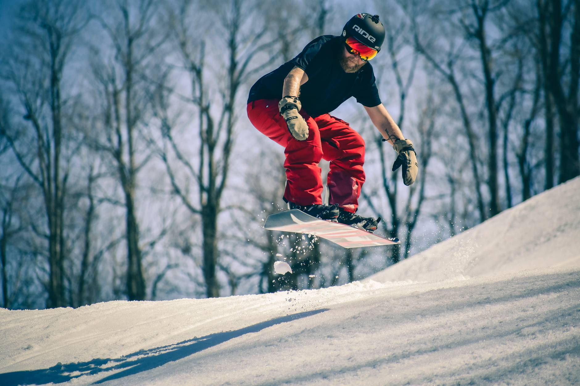 man riding on snowboard in mid air jump