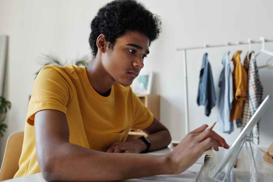 man in yellow crew neck t shirt while using tablet