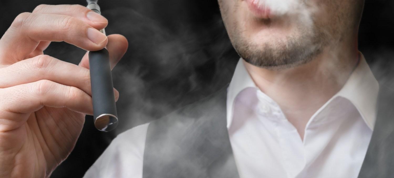 Man vaping electronic cigarette and blowing smoke.