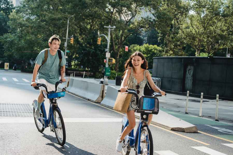 positive friends riding bicycles on city street in daylight