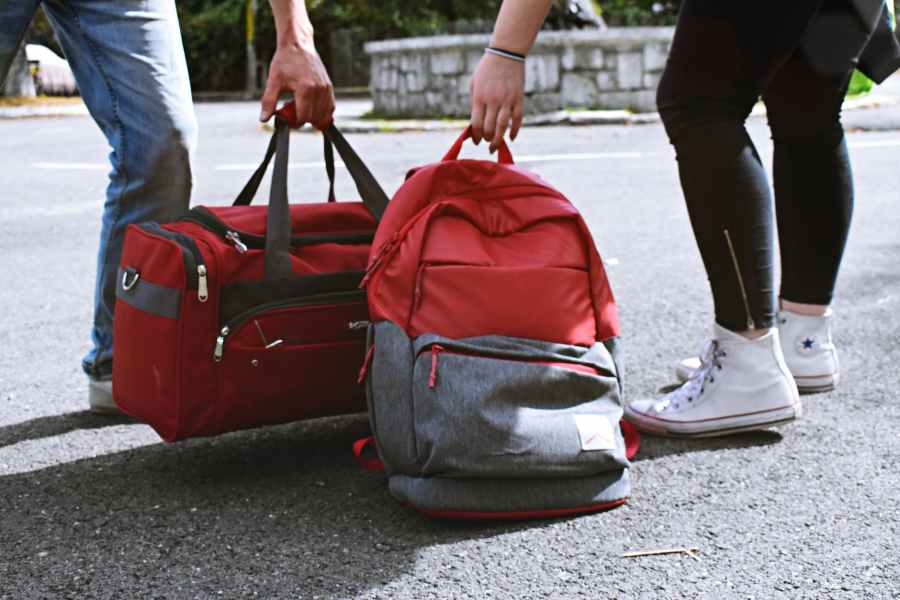 two person carrying duffel and backpack. Photo by Dids on Pexels.com
