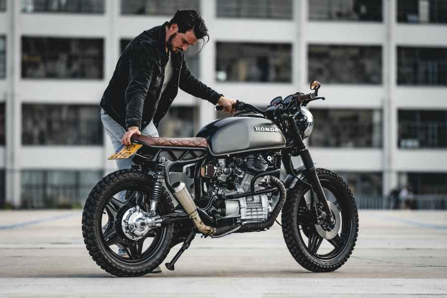 selective focus photo of man in black jacket parking black honda cafe racer motorcycle. Photo by Gijs Coolen on Pexels.com