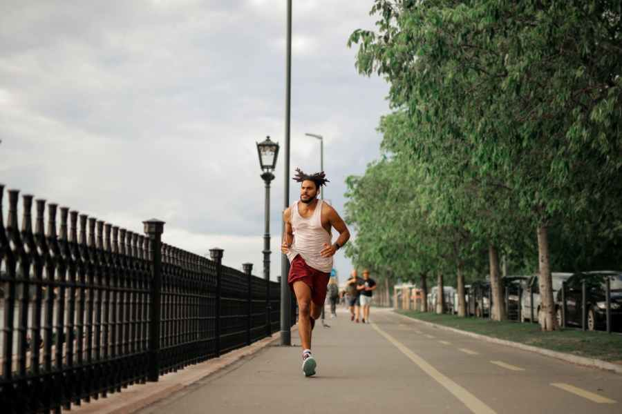 man in white tank top and red shorts running on road. Photo by Andrea Piacquadio on Pexels.com
