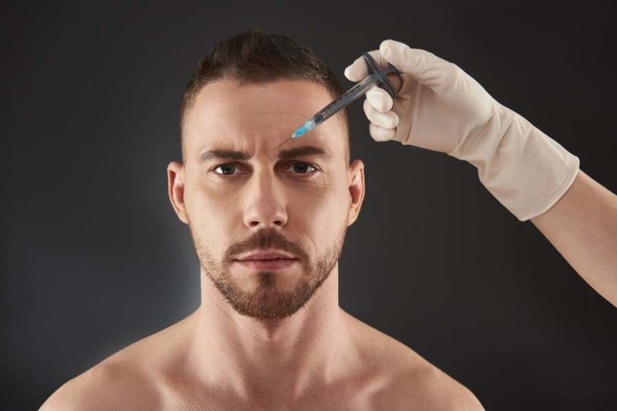 Waist up portrait of Caucasian guy looking at camera against gray background. Cropped shot of male model getting beauty injection made by cosmetologist in salon. Beauty and face care concept