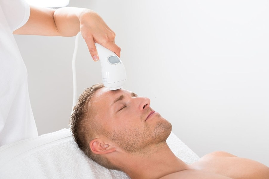 Microdermabrasion for Men: Everything You Need To Know  Young Man Receiving Laser Hair Removal Treatment At Beauty Center