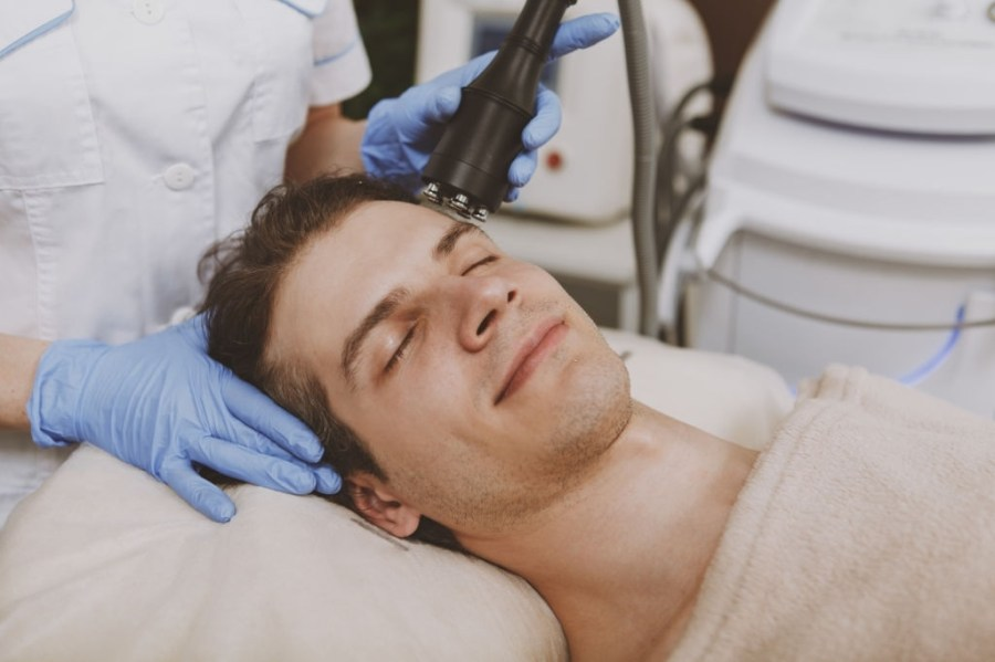 Microdermabrasion for Men: Everything You Need To Know  Happy relaxed handsome man getting facial microcurrent treatment at spa center. Attractive male client enjoying face skincare procedure by professional cosmetologist