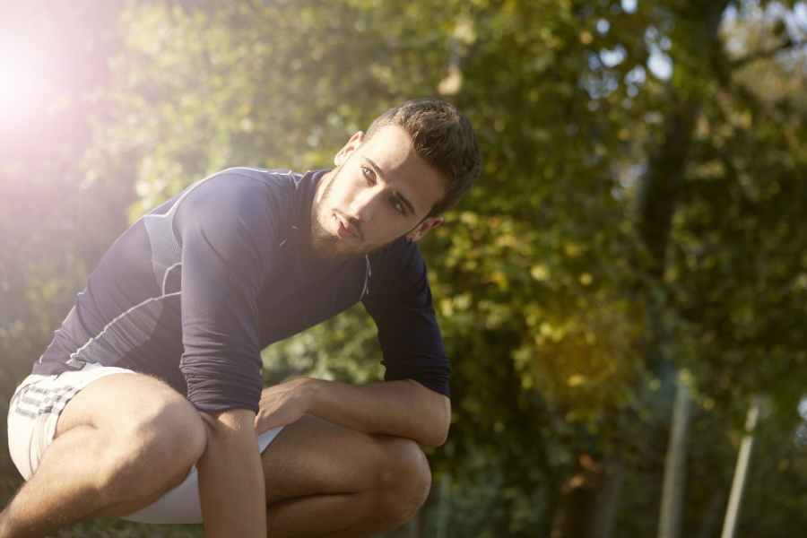 young bearded man crouching in park
