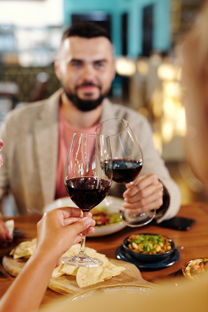 man in gray blazer holding wine glass
