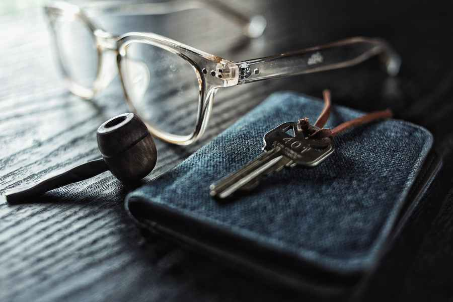selective focus photo of silver key beside brown smoking pipe and clear eyeglasses