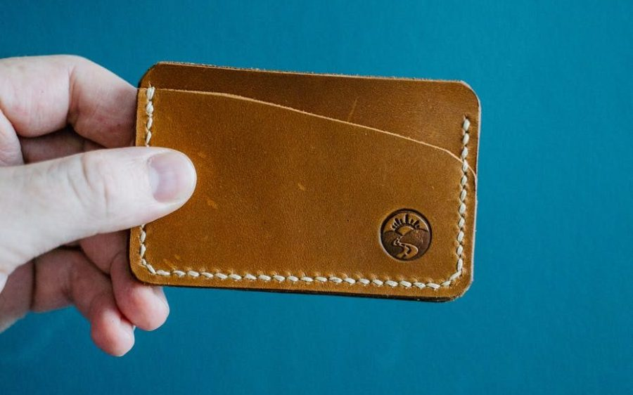 close up photo of a person s hand holding a brown leather wallet