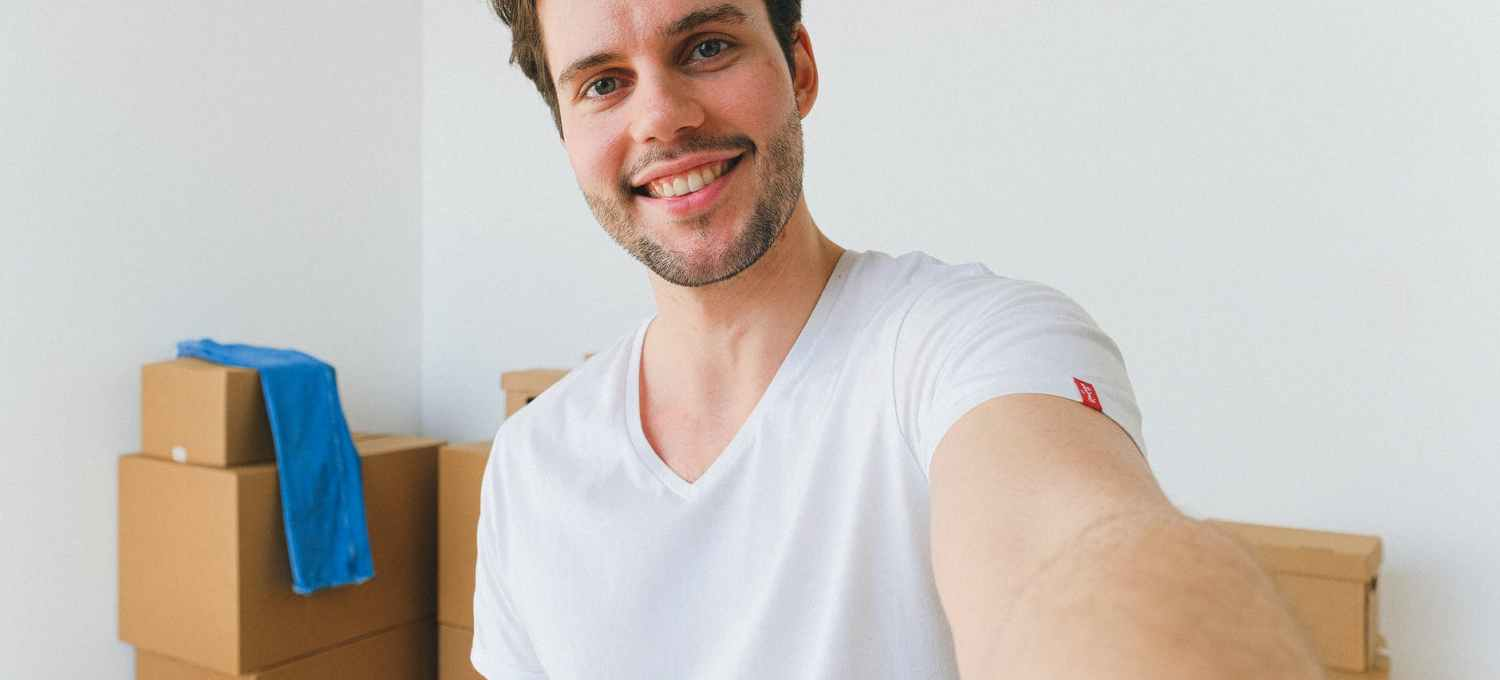 happy young guy taking selfie against carton boxes after relocation