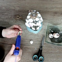 Decorating old glass bottles with twine and seashells