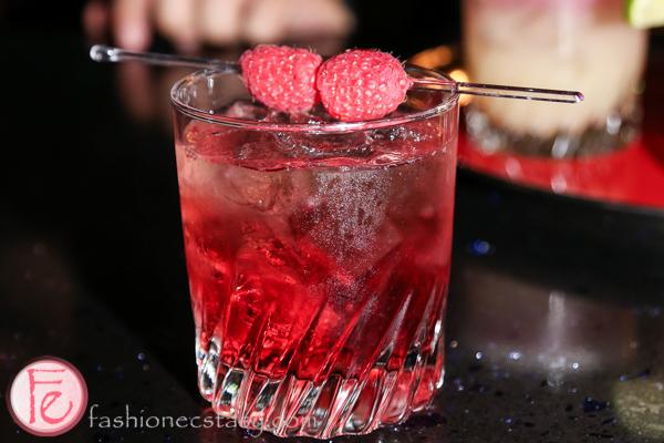 whiskey cocktail with raspberry garnish