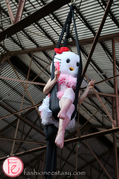 acrobatic performers on trapezes in hello kitty costume