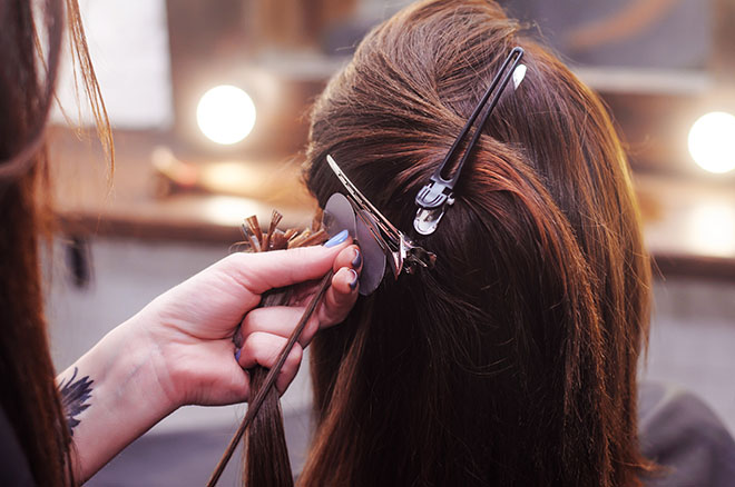 Why-Hair-Extension-Maintenance-is-a-Must-woman-getting-extensions-at-salon