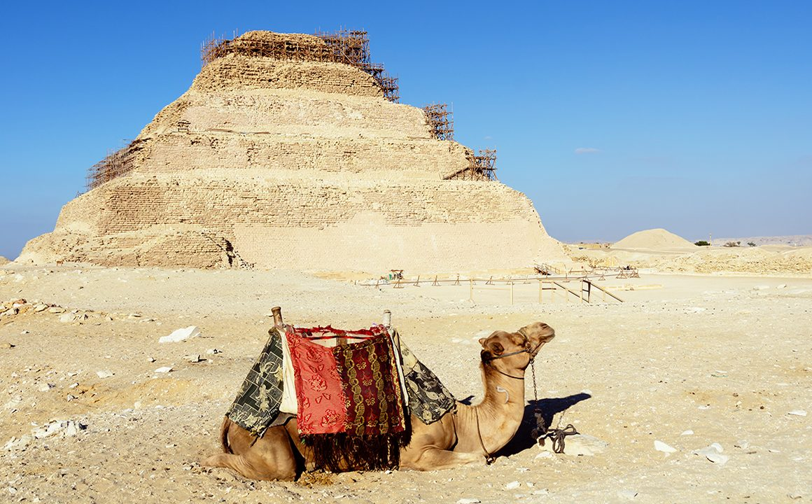 solo-traveling-to-egypt-uncommon-things-to-do-camel-sitting-in-the-sand-in-front-of-pyramid