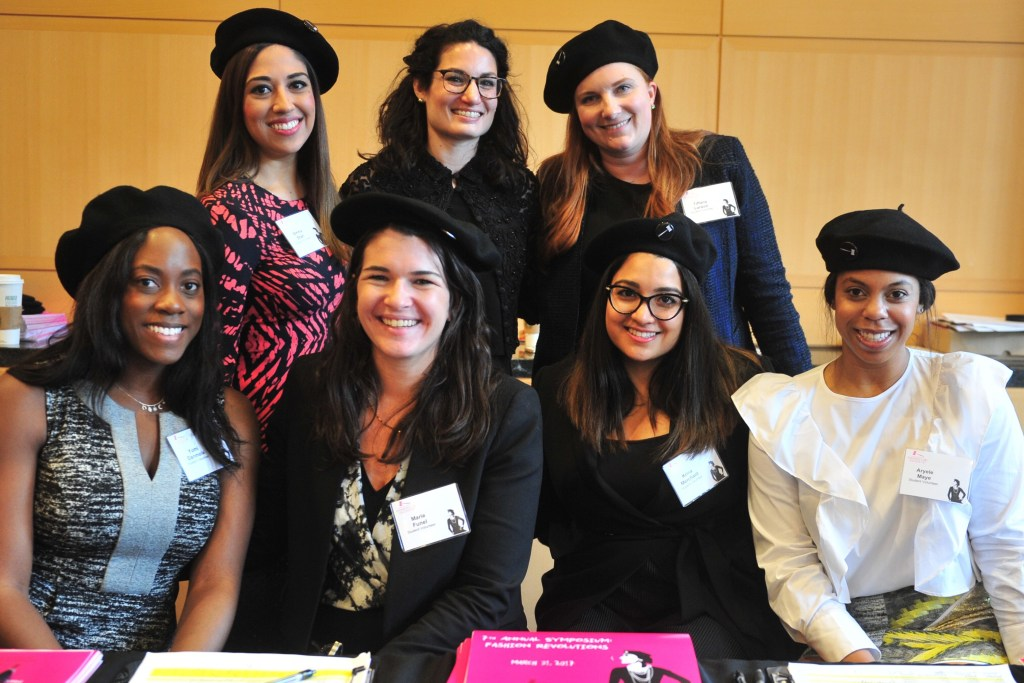 Student volunteers at the Fashion Law Institute's Fashion Revolutions symposium wear black berets bearing the Fashion Law Institute's needle-and-spool gavel logo