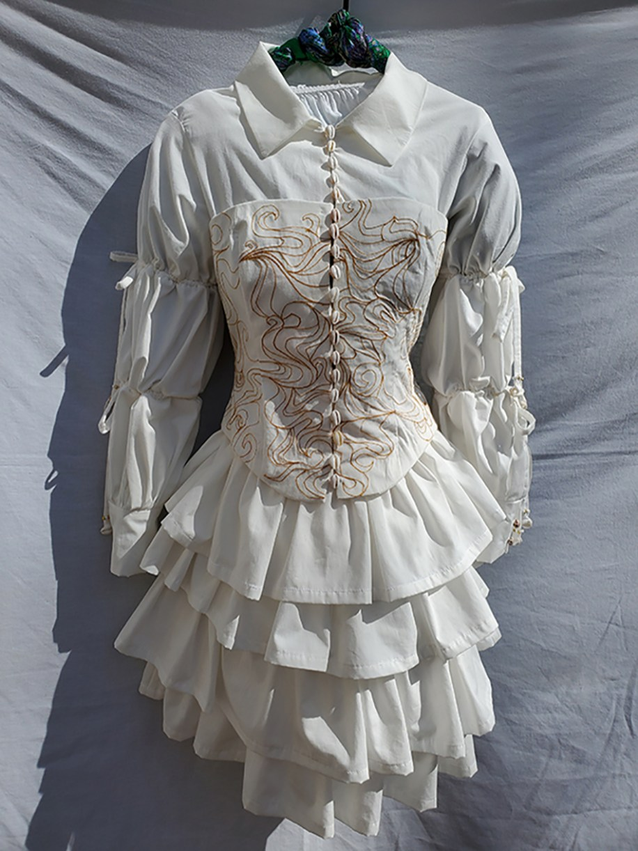 Cotton dress with adjustable sleeves, ruffle skirt, embroidered bodice, and handpicked shell closures
