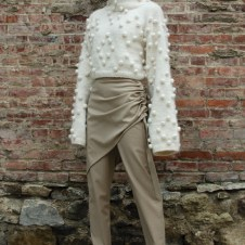 Hand knit white diamond bobble texture sweater with high neck and exaggerated sleeves, Sand sarong pant.