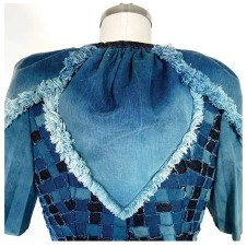 Close-up view of ombre bleached, hand-fringed, denim petal capelet.