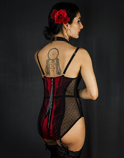 A half body back view of the red bodysuit detailed with a black lace and dot mesh. Styled with garters attached to lace thigh highs and a red rose hairpiece.