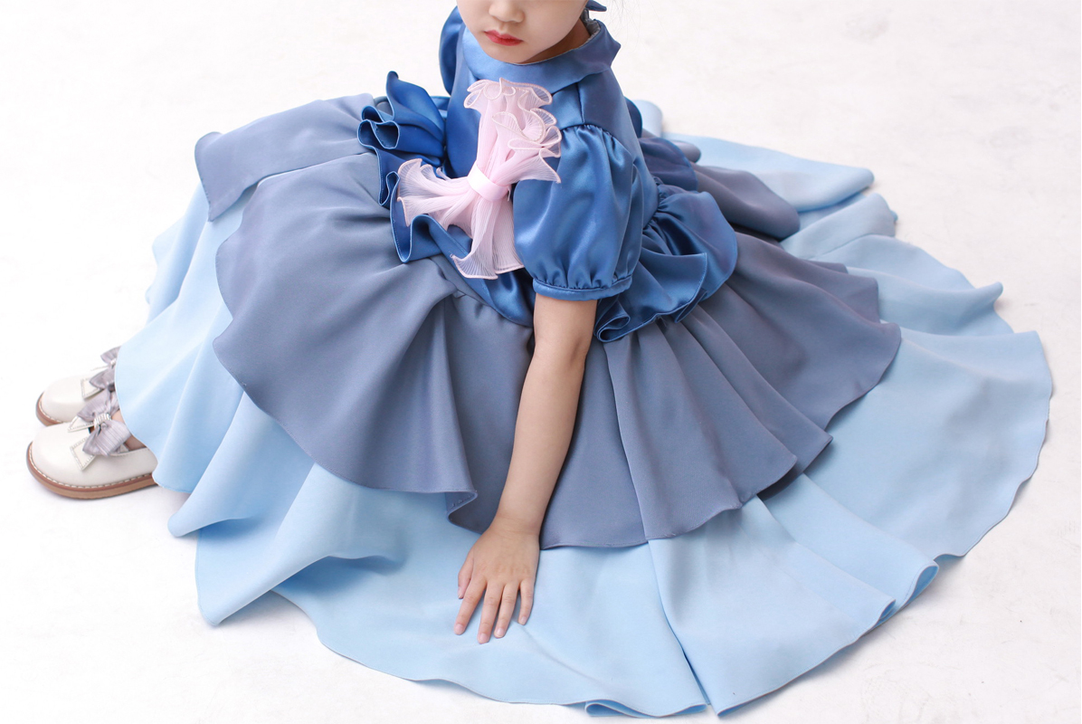 Little girl model is sitting on the white floor in a tiered blue dress with a pink bow.
