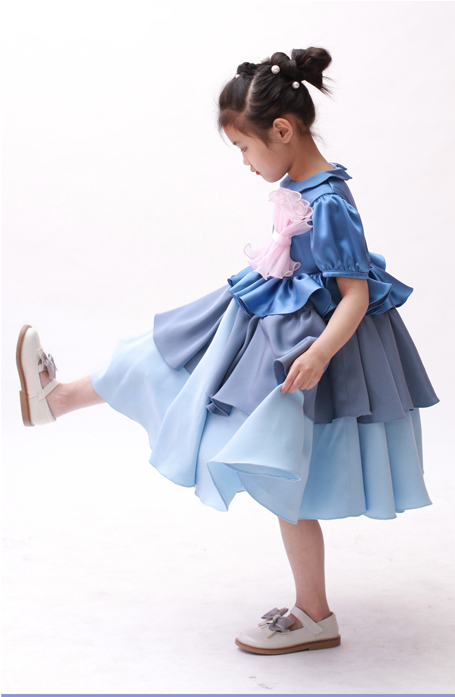 Little girl is standing with her one leg up, showing her off white shoes. She is wearing a blue dress.