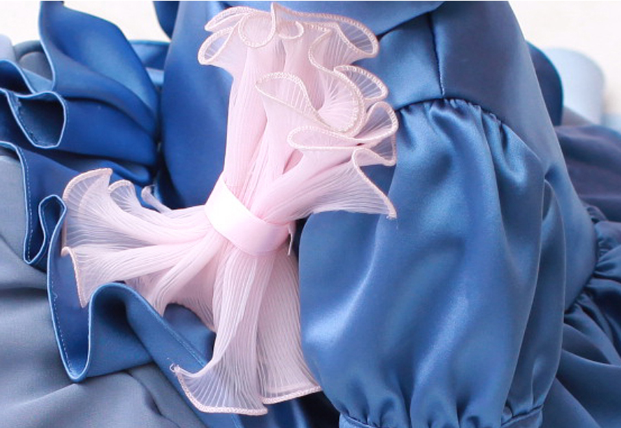 Close up photo of a pink bow on a blue dress.