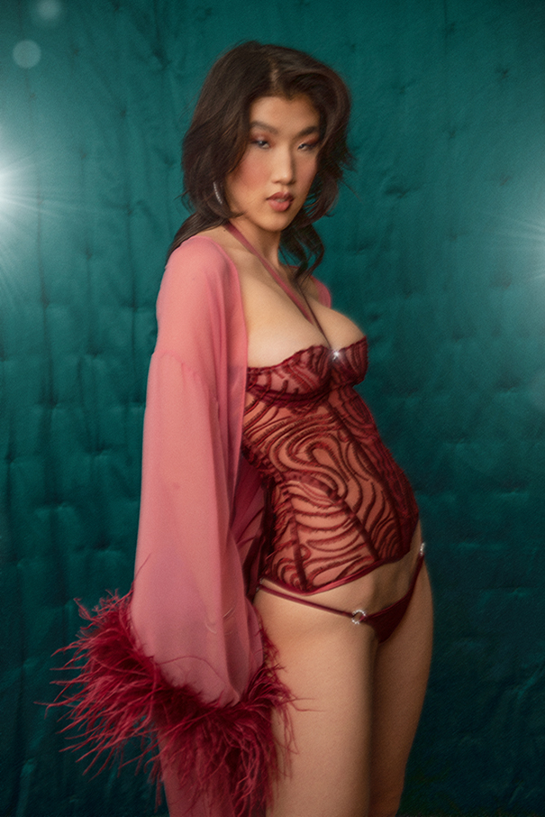 Woman standing in front of a satin teal backdrop wearing burgundy embroidered tulle bustier, burgundy silk panty, and pink silk chiffon robe with burgundy ostrich feather trim.
